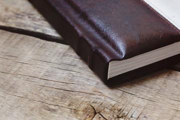 Photo album, photobook memories on a wooden table.