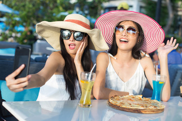 Beautiful Asian Woman have dinner at reataurant with friend, Woman using Smartphone for Selfie, People Lifestyle Concept.