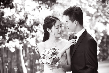 outdoor portrait of a newly-wed asian couple, black and white.