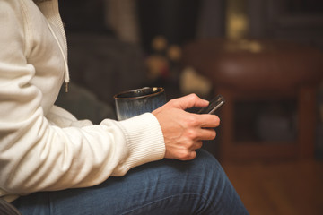 Woman Relaxing with Coffee and Using Cell Phone