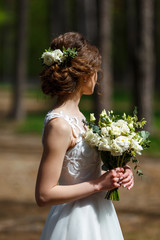 Bride with white natural flowers in her hair and wedding bouquet in forest. Portrait of attractive young woman with beautiful hairstyle and stylish hair accessory, rear view