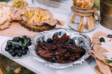 Salty and cheese bar of several kinds of cheese, grapes, olives and snacks decorated on vintage wooden table. Wedding or other holiday party outdoors