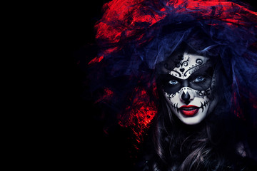 Close up studio portrait of beautiful woman with Halloween sugar skull makeup in red and black colors, wearing bridal veil. Model looking at camera. Dark, dead bride. Copy, empty space for text.