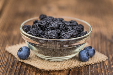 Dried Blueberries on wooden background; selective focus