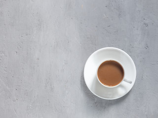 Cup of fragrant coffee on a background under the concrete. Minimalism is the view from the top. Copy space