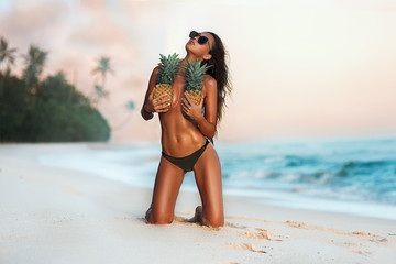 sexy beautiful girl on the beach with pineapples and palm trees with an attractive figure and belly press