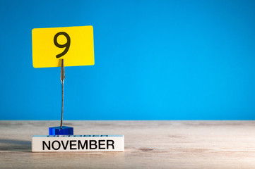 November 9th. Day 9 of november month, calendar on workplace with blue background. Autumn time. Empty space for text