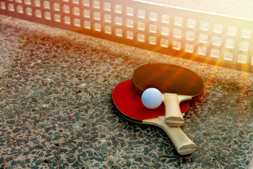 Close up of ping-pong ball with tennis rackets on stone tennis table in sunny lights, Equipment for outdoors table tennis. Outdoor sport concept.healthy lifestyle and objects concept