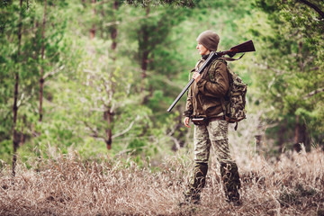 Female hunter in camouflage clothes ready to hunt, holding gun and walking in forest. Wall mural