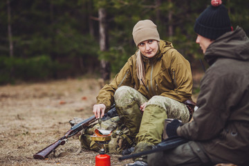 Female hunter preparing food with a portable gas burner in a winter forest.