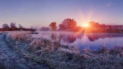 Sunrise on autumn frosty nature. Landscape of bright dawn over river. grass with hoarfrost shining on sun lights
