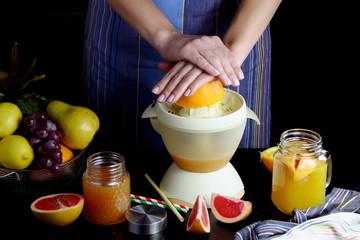 девушка выжимает сок из апельсина и грейпфрута
