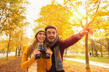 Happy young couple exploring in autumn at the park