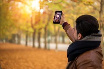 Handsome man taking selfie at a park in autumn