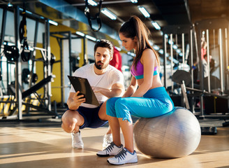 Young healthy active woman sitting on the gym ball and consulting with a personal trainer about an exercise plan.