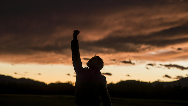 Man raising his fist against sunset sky