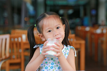 Beautiful cute little girl drinking glass of fresh milk. Healthy nutrition for kids.