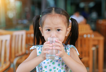 Asian little girl is drinking a water from glass with looking at camera.