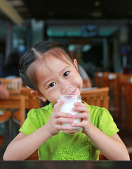 Asian child hold a glass of milk and smile in restaurant at the morning.