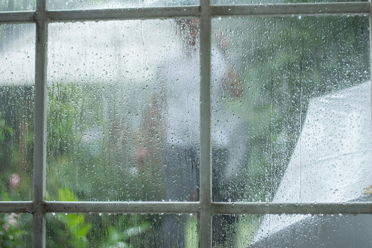 Abstract blurred of men under umbrella seen through raindrops on window glass, blurred. Concept of seasons