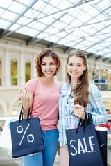 Two happy girls with shopping bags enjoying seasonal sale in the mall