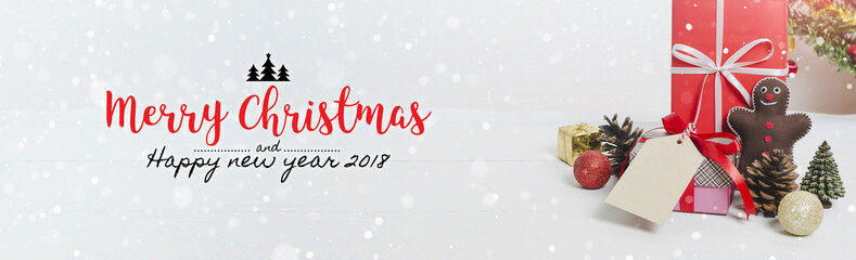 Christmas and New Year holidays gift box with decorative ornament on white wooden table with falling snow effect banner.Merry Christmas & Happy New Year 2018.Gifts and congratulations concept.