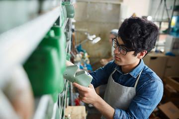 Shoemaking specialist choosing workpiece form of footwear from shelf in workshop Wall mural