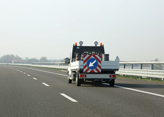 van for highway maintenance with the arrow in the traffic signal