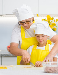 Mother teaches her son how to cook food in the kitchen