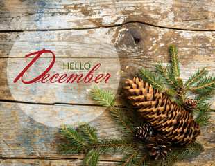 Hello December wallpaper with fir tree and pine cones on rustic wooden background