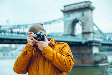 young man photographer shooting old bridge on background