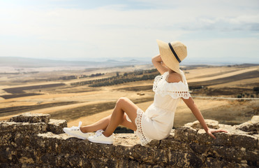 A girl in a white dress is looking at a meadow. Travel, rest, vacation. Tunisia.