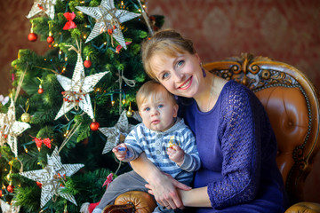happy mother with baby sitting near a festive Christmas tree