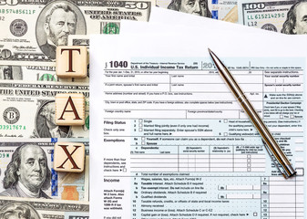 """Word """"tax"""" written by wooden cudes with tax form and pen on background of dollar bills. Business concept."""