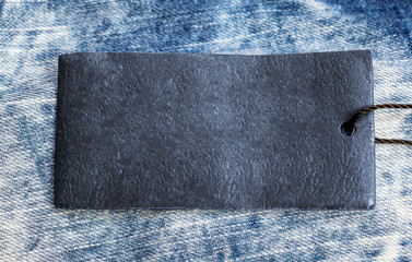 Blue paper label on the light blue jeans texture. Close up.