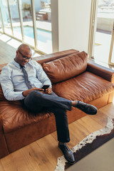Businessman sitting on lounge using mobile phone