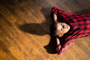 Portrait of cute boy relaxing on wooden floor