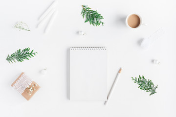 Christmas composition. Cup of coffee, notebook, thuja branches on white background. Christmas, winter, new year concept. Flat lay, top view, copy space