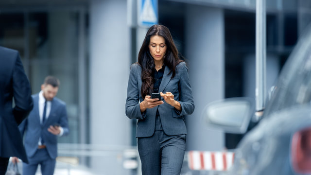 Business Woman in the Tailored Suit Walking on the Busy Big City Street in the Business District, Checks Her Smartphone. Confident Woman on Her Way to do Big Business.