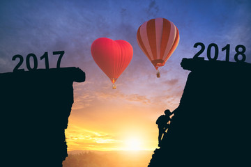 Young man climbing between 2017 and 2018 years with two hot air balloon . Happy new years concept