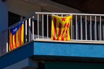 The national flag of Spain  hang on the balcony in a street of town .