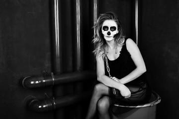 Halloween skull make up girl wear in black against sitting on red barrel at studio.