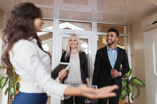 Hotel Receptionist Meeting Business Couple In Lobby, Businesspeople Group Man And Woman Guests Arrive Entrance With Suitcase