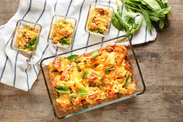 Baking dishes with delicious sausage casserole on table