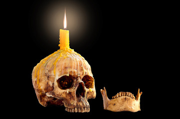 Skull with candle flame on head and jaw Isolated on black background and Space for message
