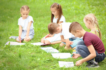 Cute little children drawing pictures on green grass