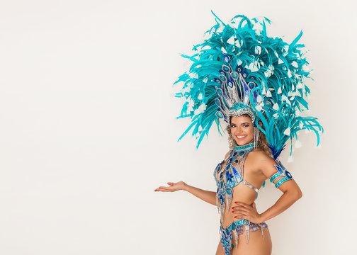 Beautiful brazilian samba dancer smiling and showing something - Copy space