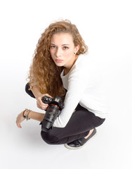 young girl with photo camera sitting on white background