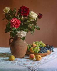Bouquet of roses in a jug and a dish with grapes and peaches.