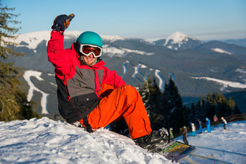 Happy male snowboarder smiling showing thumbs up sitting on the snow in the mountains resting after riding copyspace happiness recreation winter sports resort leisure lifestyle